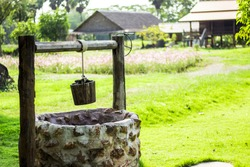 Artesian well with wooden drive shaft bucket in garden