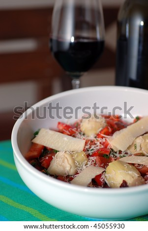 Artichoke heart salad with a glass of red wine (ingredients:red-be ll pepper,parmesan cheese,sun-dried tomato,fresh tomato and dill with olive oil and lemon juice) - stock photo