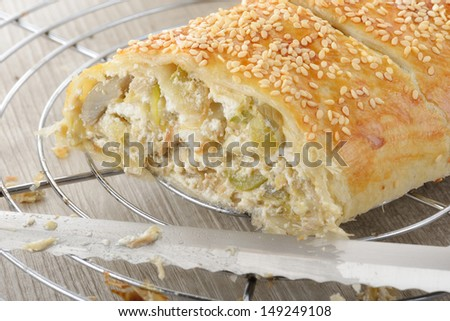 Artichoke pie with sesame seeds on table laid
