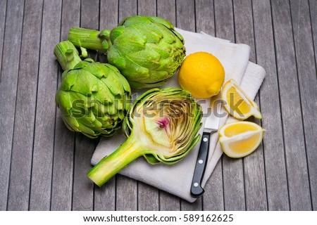 Artichokes and lemons on wooden table with napkin and knife. Artichokes have one of the highest antioxidant capacities reported for vegetables and potentially lower cholesterol levels.