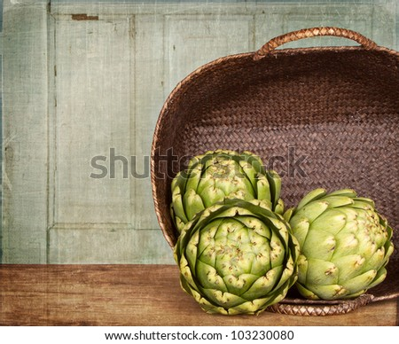 artichokes spilling out of a basket, with a grunge background - stock photo