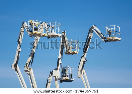 Articulated boom lift. Aerial platform lift. Telescopic boom lift against blue sky. Mobile construction crane for rent and sale. Maintenance and repair hydraulic boom lift service. Crane dealership