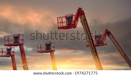 Articulated boom lift. Aerial platform lift. Telescopic boom lift with sunset sky. Mobile construction crane for rent. Repair hydraulic boom lift service. Crane dealership. Safety use of machinery.