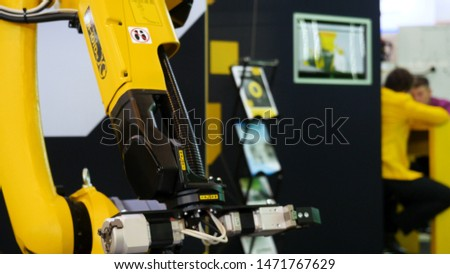 Artificial automated manufacturing smart robot of yellow color moving its hand, modern technologies concept. Media. Robot arm moving slowly.