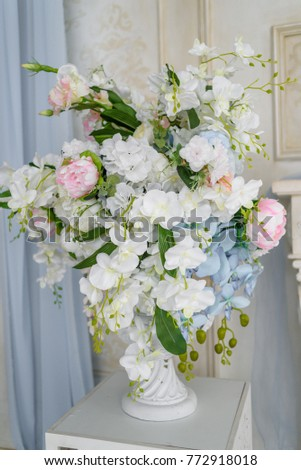 Artificial Bouquet Of Flowers In White Antique Vase Near Wall In The