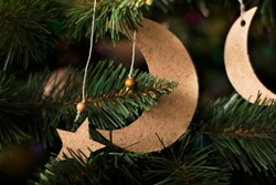 Artificial Christmas tree with handmade homemade cardboard decorative stars and a crescent moon.