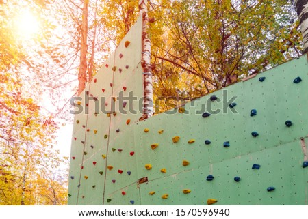 Artificial climbing wall with hooks for kids and adults in natural amusement Park on sunny day. Concept of healthy lifestyle, fitness, extreme sports, development of endurance.