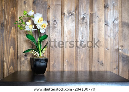 Artificial flower in a vase standing on a wooden pedestal on a background of a wooden wall