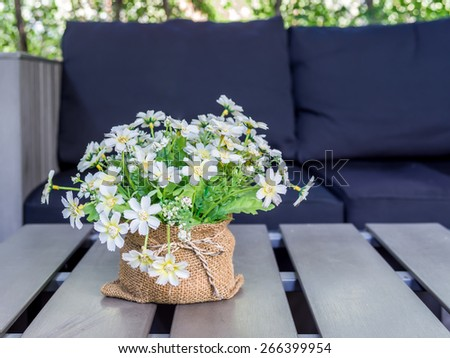 Artificial flower on desk top with black couch background