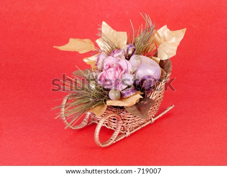Artificial flowers in a sleigh on red background.