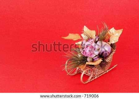 Artificial flowers in a sleigh on red background with space for copy.