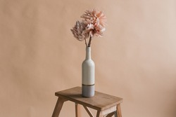 Artificial flowers in a vase. Studio photography of flowers. Decorative flowers with own hands. A minimalist bouquet of artificial flowers