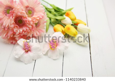 artificial flowers, pink flowers, white tulips and yellow tulips on light blue background.