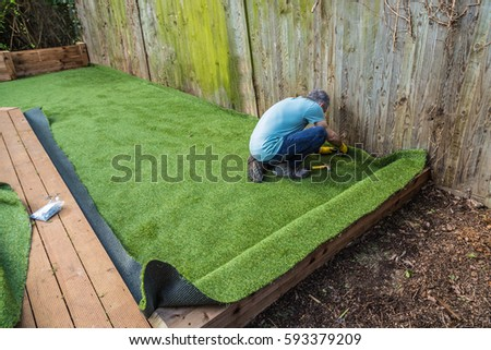 Artificial grass being installed, added next to wooden decking. It has been cut to size and rolled out and laid and is being nailed down. the installer has a hammer and nails.