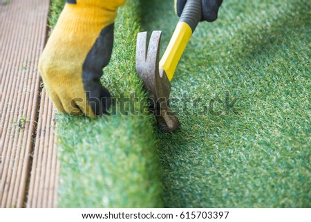 Artificial grass, turf installation alongside decking. A hammer in being used to nail the turf into place. A yellow work glove can be seen. #615703397