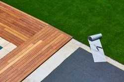 Artificial grass turf installation in deck garden with tools and joint roll