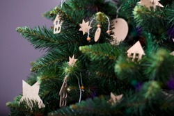 Artificial green Christmas tree, with  handmade Christmas decorations. Cardboard decorative stars, small houses and a crescent moon.