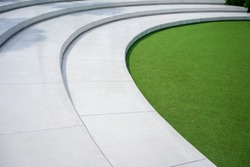 Artificial green grass with white concrete stairs for nature theme  decoration concept. Outdoor amphitheater.