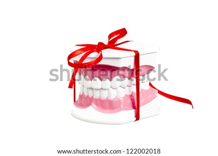 Artificial human jaw with white teeth represented as a gift with a red ribbon/New smile gift