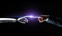 artificial intelligence, future technology and communication concept - robot and human hand connecting fingers on black background with flare