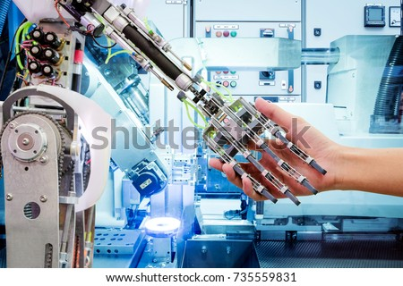 Artificial Intelligence handshake with humans on industrial robotics in blue tone color background, The robot has a role to work replacing humans in modern industries, industry 4.0 concept