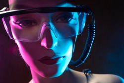 Artificial intelligence robot face. Cyborg woman has glasses on her face. Close-up. Concept - creation of robots with artificial intelligence. Wires next to the face of a humanoid cyborg. Cyborg sale