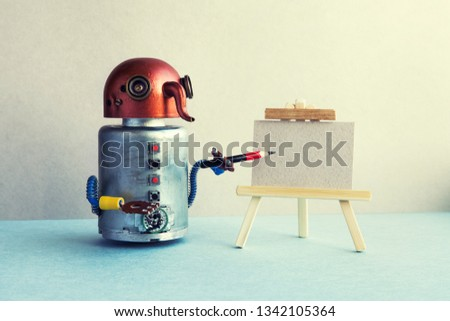 Artificial intelligence robotic concept. Funny robot artist begins to create a drawing with a pencil. White paper template, wooden easel. Advertising poster studio school of visual arts. copy space
