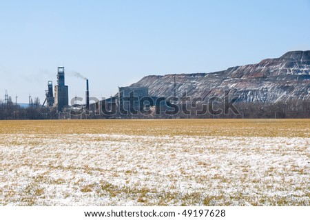 Artificial man-made rock near coal mine in Ukraine with winter field on foreground