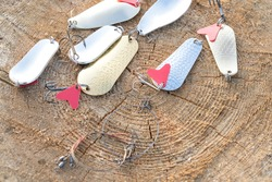 artificial metal baits on a wooden background. Homemade fishing gear. baits for catching large predatory fish. Items are made of different metal alloys of different colors and shapes
