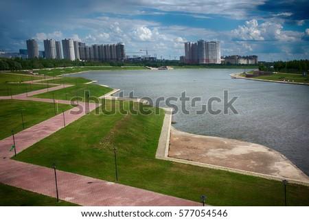 Artificial pond on outskirts of big city (break area, recreation site; recreation zone; recreational island) with walking paths (paved sidewalk, promenade). Kazakhstan #577054546