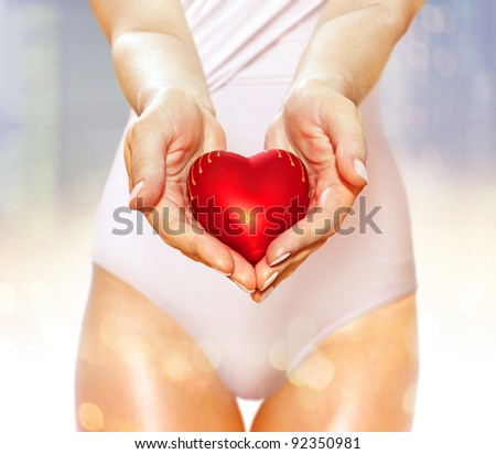 artificial red heart on hands of beautiful woman