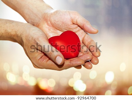 artificial red heart on hands of man