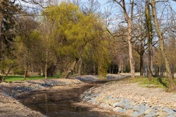 Artificial riverbed. Trees grow around the water and there is a large park.