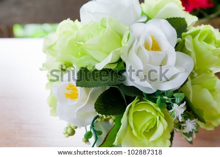 Artificial rose flowers bouquet on wood table