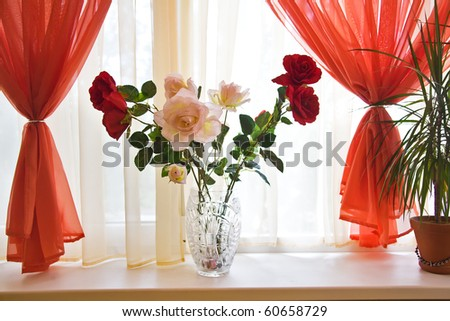 Artificial roses bouquet on window sill framed with red curtains
