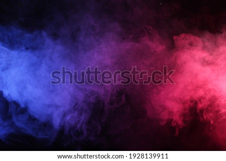Artificial smoke in red-blue light on black background in darkness