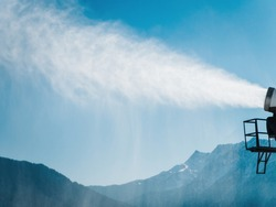 Artificial snow scatters from the muzzle of a snow cannon against the backdrop of blue sky and mountains