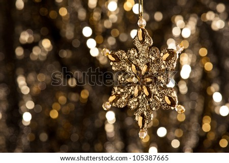 Artificial Snowflake in gold shining over a golden background
