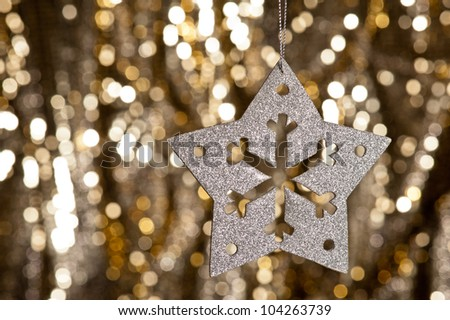Artificial Snowflake in Silver shining over a golden background
