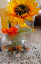 artificial sunflowers together with an orange artificial flower in a decorative glass bowl with decorative stones on a glass table in an interior setting