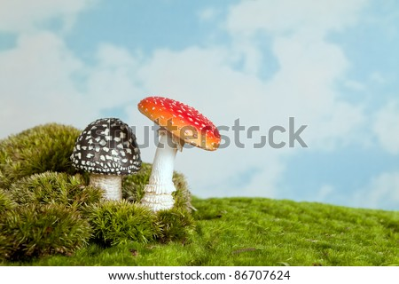 Artificial toadstools standing on real moss as an background for fairytale scenes