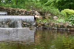 artificial waterfall in public park . High quality photo