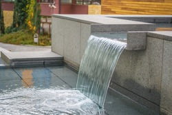Artificial waterfall on the city background.