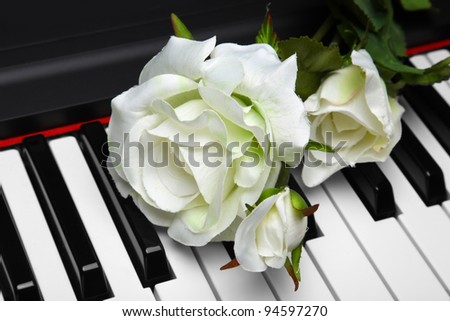 Artificial white rose on piano keyboard. Very shallow depth of field.