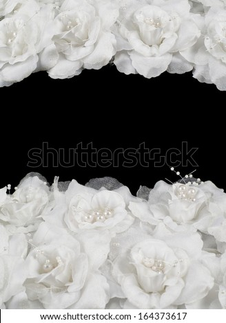 Artificial white roses over black background