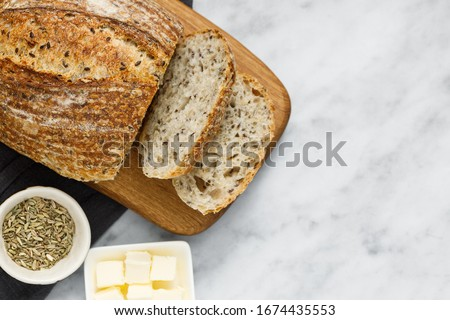 Artisan bread and butter on napkin, top view. Fresh sliced bread and organic butter for breakfast. Rustic sourdough bread on white marble table.