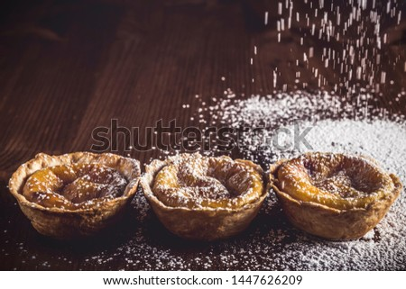 Artisan pastries from Belem, traditional dessert from Portugal. Delicious homemade Belem cakes that are sprinkled with icing sugar on a rustic dark wood table. Cream cakes.