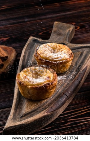 Artisan pastries from Belem, traditional dessert from Portugal. Delicious homemade Portuguese Cake - Pasteis de Belem or Nata sprinkled with icing sugar on a rustic dark wood table Foto stock ©