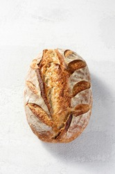 Artisan sourdough homemade loaf of bread on grey concrete background. Natural light with soft shadows, closeup view