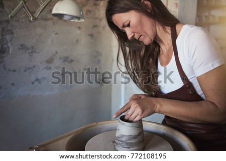 Artisan using a sculpting tool to shape a piece of clay turning on a pottery wheel while sitting in her ceramic workshop